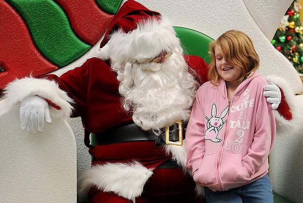Sidda Soudek visits with jolly ol' St. Nick inside Oakwood Mall Friday. (Staff Photo by BONNIE VCULEK)