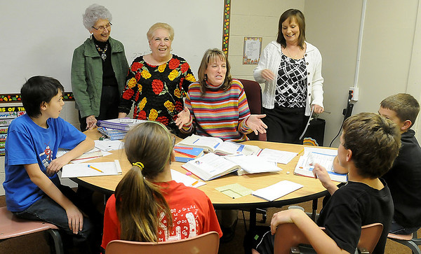 """Beverly Voth, Joyce Fales, Diane Highfill and Kristi Hilburn (top, from left) smile as Mrs. Highfill receives the """"Successful Students"""" classroom teacher grant in the amount of $1502 Wednesday from the Kremlin-Hillsdale Academic Enrichment Foundation. (Staff Photo by BONNIE VCULEK)"""
