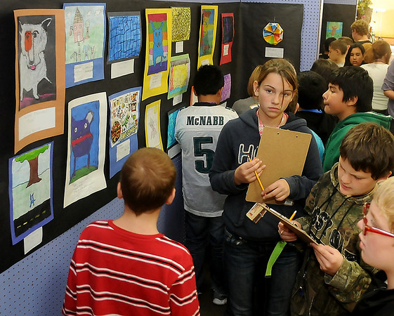 With clipboards in hand, Monroe Elementary School's fifth grade students critique art work during a hands-on lesson at Park Avenue Thrift Wednesday. (Staff Photo by BONNIE VCULEK)