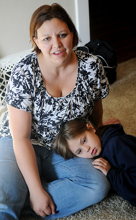 Weslie White answers questions about the adoption of her three children as Alana, 9, rests her head on her mother's leg Friday. (Staff Photo by BONNIE VCULEK)