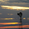 Streaks of sunlight appear beyond a windmill near Enid Sunday. (Staff Photo by BONNIE VCULEK)