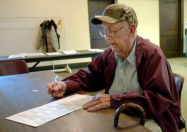 Lynn Bowen, 101, of Hillsdale, fills out his ballot as he votes at the Carrier Congregational Church Tuesday. (Staff Photo by BILLY HEFTON)