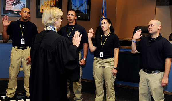 The Honorable Linda Pickens (front) swears four new officers into duty for the Enid Police Department Thursday at the City of Enid Council Chambers.<br /> The officers (from left) are Earl Smith III, Joshua Allison, Michele James and Vladimir Iglesias. (Staff Photo by BONNIE VCULEK)