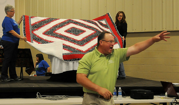 A Lippard Auctioneer (front, right) accepts a bid on a pieced, hand quilted black, red, and white flying geese log cabin pattern design and donation by Henry and Clarabelle Buller Saturday. One quilter used 1600 pieces to complete the beautiful 99 inch x 99 inch item for the Oklahoma Mennonite Relief Sale at the Chisholm Trail Expo Center Pavilion. (Staff Photo by BONNIE VCULEK)