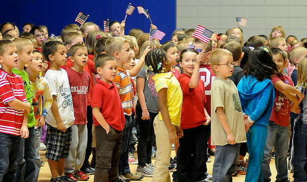 """Prairie View Elementary School students wave American flags as they sing """"Proud to Be an American"""" during the Veterans Day Assembly Friday. (Staff Photo by BONNIE VCULEK)"""