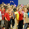 "Prairie View Elementary School students wave American flags as they sing ""Proud to Be an American"" during the Veterans Day Assembly Friday. (Staff Photo by BONNIE VCULEK)"