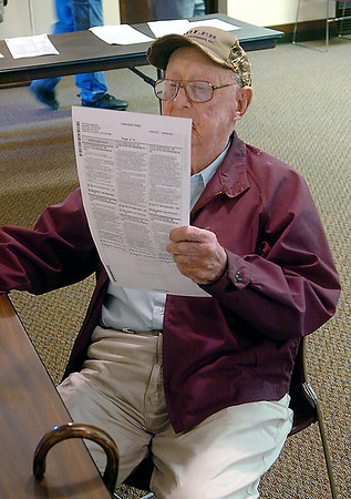 Lynn Bowen, 101, of Hillsdale, reads over his ballot as he votes at the Carrier Congregational Church Tuesday. (Staff Photo by BILLY HEFTON)