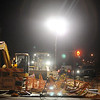 Workers use spotlights as they complete underground repair at the corner of W. Maine and N. Independence near the Renaissance construction site late Thursday evening. (Staff Photo by BONNIE VCULEK)