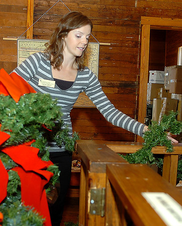 Sarah Owens hangs Christmas decorations inside the land office at the Humphrey Heritage Village Wednesday. (Staff Photo by BILLY HEFTON)