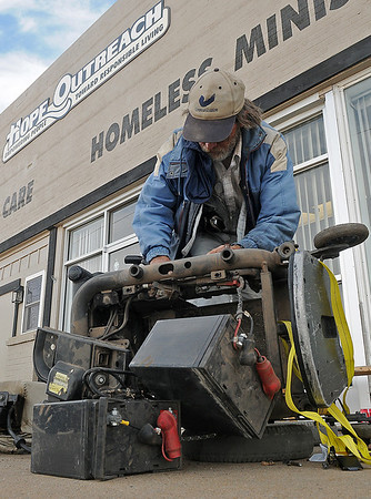 Stephen Hudson, a veteran of the Vietnam War, works on his power chair outside the Hope Outreach Homeless Ministry Center Tuesday. (Staff Photo by BONNIE VCULEK)