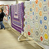 Beautiful quilts await auction during the Oklahoma Mennonite Relief Sale Saturday at the Chisholm Trail Expo Center Pavilion. (Staff Photo by BONNIE VCULEK)