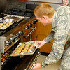 Lt. Joe Roy pulls a tray of cookies out of the oven Tuesday as part of Operation Cookie Cutter. Volunteers bakes cookies to send to troops from Vance Air Force Base deployed overseas. (Staff Photo by BILLY HEFTON)