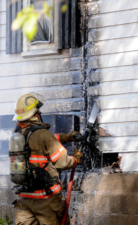 Lt. Rick Griffith uses a booster line as he battles a house fire at 414 E. Maple Friday. (Staff Photo by BONNIE VCULEK)
