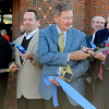 Mayor Bill Shewey (center) hands his commemorative scissors to Tom Sailors Thursday during the Enid Convention Hall Grand Re-Opening ribbon cutting ceremony. (Staff Photo by BONNIE VCULEK)