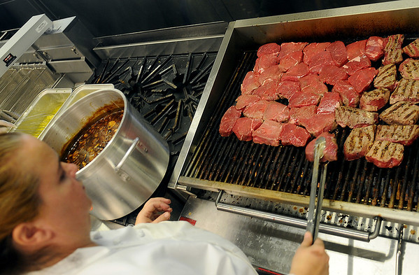 """Bobbie Pacula prepares Chef James Morrow's """"Sirloin with Hunter's Sauce"""" for more than 300 guests Thursday during the grand re-opening of the Enid Convention Hall. (Staff Photo by BONNIE VCULEK)"""