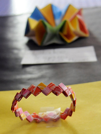 Zack Patterson's origami starburst bracelet appears below an origami U.F.O flower designed by Blake Wednesday at the Park Avenue Thrift fifth grade art exhibit. (Staff Photo by BONNIE VCULEK)