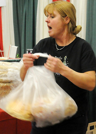 Shannon Campbell, from Styria Bakery, quickly wraps three loaves of fresh bread for one of her customers during Home for the Holidays at the Chisholm Trail Expo Center Saturday. (Staff Photo by BONNIE VCULEK)