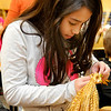 Prairie View fourth grader, Sophie Taiclet, weaves stocks of wheat Tuesday to create a wheat angel. (Staff Photo by BILLY HEFTON)