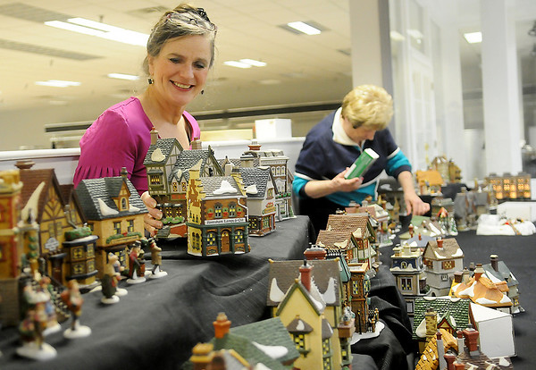 Tary Davis and Nancy Jewell arrange more than 300 pieces of Jewell's Department 56 Village collection Friday at Oakwood Mall. The Enid Arts Council with cooperation from Oakwood Mall and Park Avenue Thrift are displaying the unique, retired collection in The Bridal Shop windows throughout the holidays. (Staff Photo by BONNIE VCULEK)