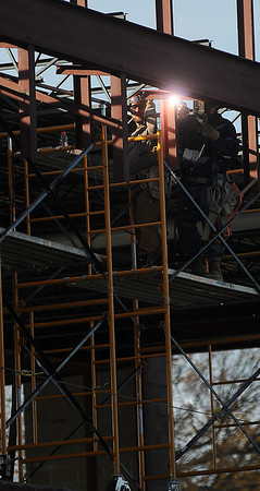 Welders secure a piece of metal Thursday as work continues on the Enid High School University Center. (Staff Photo by BONNIE VCULEK)