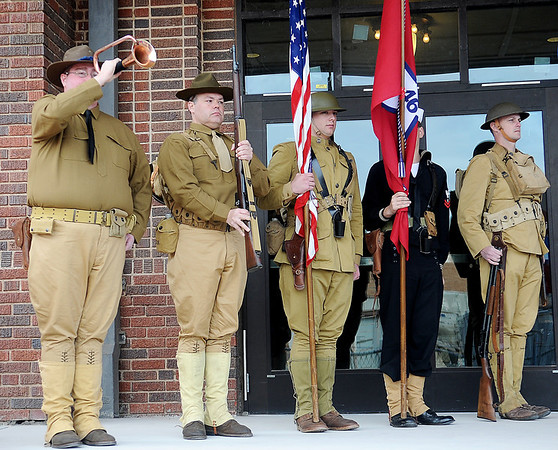 World War I re-enactors stand at attention as Cody Jolliff (left) plays revelry during the grand re-opening ceremony outside Convention Hall Sunday. Re-enactors (from left) are Jolliff, Matt Reed, Christian Rountree, Nathan Buckendorf and Mike Buckendorf. (Staff Photo by BONNIE VCULEK)
