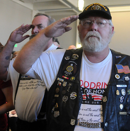 "Vietnam Veteran Keith Walch (right) and James Thompson (back, left) salute as the Enid High School ROTC posts the colors during the Woodring Wall of Honor ""Welcome Home"" ceremony for the American Veterans Traveling Tribute Vietnam Wall Friday at Convention Hall. (Staff Photo by BONNIE VCULEK)"