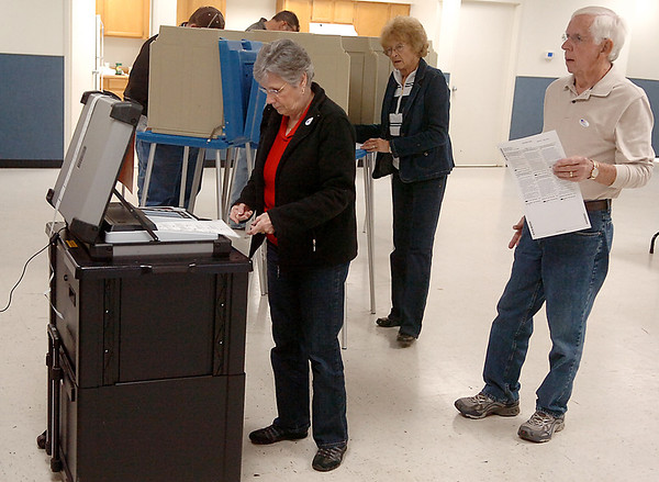 Voters feed their ballots into the voting machine at the Kremlin FWZ Community Center Tuesday. (Staff Photo by BILLY HEFTON)