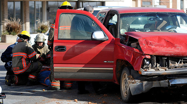 Enid emergency personnel tend to a man involved in an accident at the intersection of 2nd and Broadway Monday. (Staff Photo by BILLY HEFTON)