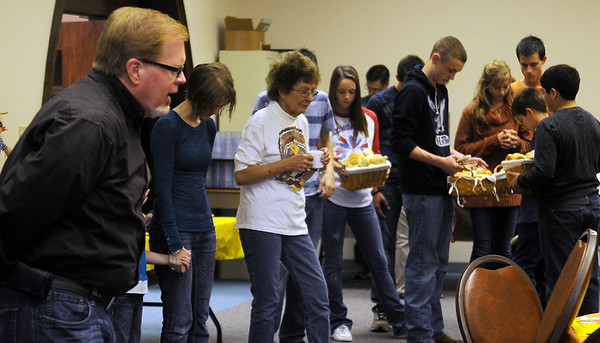 Members of the First Baptist Church and guests pause for a Thanksgiving Day prayer before the meal Thursday. Approximately 600 dine-in and carry out meals were prepared by volunteers from 11 a.m.-1 p.m. (Staff Photo by BONNIE VCULEK)