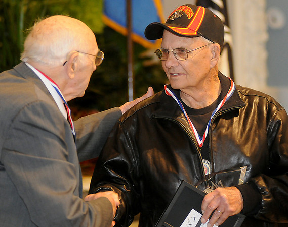 Tom LaMunyon (left), Legacy Veteran for the U.S. Army, congratulates Arlo Becker, Legacy Veteran for the U.S. Marine Corps, Sunday during an awards ceremony at Convention Hall. (Staff Photo by BONNIE VCULEK)