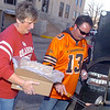 Kathy Hughes and Wade Patterson load a grill with hotdogs during a Bedlam Cookout Wednesday at the Garfield County Courthouse. (Staff Photo by BILLY HEFTON)