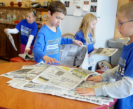 Brooklyn Phillips, Landon Schultz, Adi Betz and Daniel Voth (from left) arrange newspapers at the Hope Outreach homeless shelter Tuesday. The second grade students, under the direction of Gretchen Streck, sang at the shelter and thrift store before folding newspapers as part of their  community service project. (Staff Photo by BONNIE VCULEK)