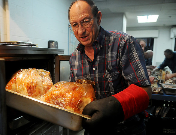 Leroy Patocka removes two of nineteen turkeys from the oven at St. Francis Xavier Catholic Church Leven Center kitchen Wednesday as the Knights of Columbus prepare the meat for the annual community Thanksgiving meal. More than 600 meals will be served at St. Francis and the First Baptist Church from 11 a.m.-1 p.m. today and 100 evening meals at the Salvation Army, beginning at 6 p.m. (Staff Photo by BONNIE VCULEK)