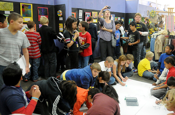 Monroe Elementary School teacher, Traci Layton (top, center), takes a photograph while fifth grade students design a giant mural and critique different artists' work during an interactive, hands-on class at Park Avenue Thrift. (Staff Photo by BONNIE VCULEK)
