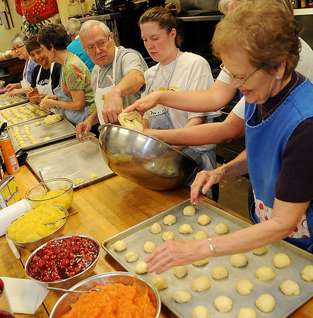 Fred Mochon (center), a Knights of Columbus member, assists the Ladies Auxiliary as they make 180 dozen kolaches Saturday at Our Daily Bread for the organization's annual holiday bake sale. The fruit-filled treats include apricot, cherry, pineapple, prune and poppy seed. During the two day event, the ladies prepare and bake the kolaches, 65-70 pecan pies and 35 pumpkin pies. (Staff Photo by BONNIE VCULEK)