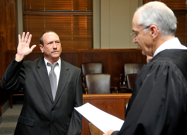 Reese Wedel takes the oath of office as a county commissioner from Hon. Judge Dennis Hladik Thursday at the Garfield County Courthouse. (Staff Photo by BILLY HEFTON)