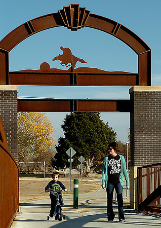 Angela Lyon crosses the pedestrian bridge of the news trail system Monday afternoon with her son, Harrison, as temperatures approached 70 degrees. (Staff Photo by BILLY HEFTON)