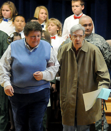 JoAnn McGuire (left) escorts her aunt, Wanda Hyland (right) back to her seat during the Prairie View Elementary School Veterans Day Assembly Friday. Hyland, 88, served in the United States Navy during World War II and was among the honored Veterans and Military Personnel who received certificates from the student body. (Staff Photo by BONNIE VCULEK)