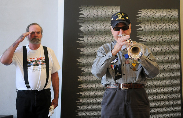 """Dr. Joe Bryant plays Taps as James Thompson salutes during a moment of silence for POW/MIA miitary service members Friday at the Woodring Wall of Honor """"Welcome Home"""" ceremony for the American Veterans Traveling Tribute, which honors 58,272 Vietnam Veterans who lost their lives in the service of their country. (Staff Photo by BONNIE VCULEK)"""