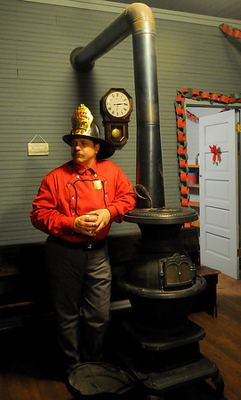 Firefighter Todd Hayes pauses near the Turkey Creek School pot belly stove Friday during Christmas in the Village at the Cherokee Regional Heritage Center. (Staff Photo by BONNIE VCULEK)