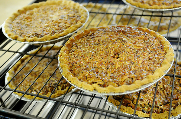 Hot pecan pies cool on racks Friday at Our Daily Bread as members of the Ladies Auxiliary prepare the homemade sweet treats for their annual fundraising event. (Staff Photo by BONNIE VCULEK)