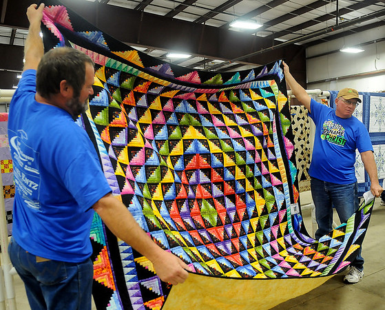 Oklahoma Mennonite Relief Sale volunteers prepare The People's Choice Award for auction Saturday at the Chisholm Trail Expo Center Pavilion. (Staff Photo by BONNIE VCULEK)