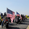 "Veterans unfurl American and military flags as they begin the final few miles into Enid for the Woodring Wall of Honor ""Welcome Home"" ceremony for the American Veterans Traveling Tribute honoring Vietnam Veterans Friday. (Staff Photo by BONNIE VCULEK)"