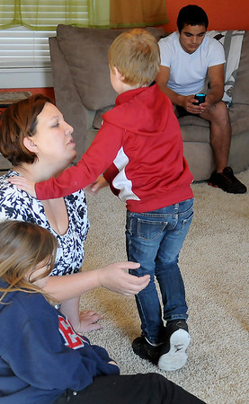 Weslie White relaxes with her children Alana, 9, Tyler, 5, and Alex, 17, Friday in their home in Hunter. White adopted the three children and currently cares for two additional foster children. (Staff Photo by BONNIE VCULEK)