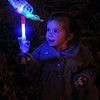 Little Sophie Williams glances at her color-changing wand Friday during Enid Lights Up the Plains. (Staff Photo by BONNIE VCULEK)