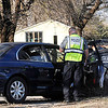 An Enid police officer works the scene of a car vs house accident Thursday west of Garland on US 412. (Staff Photo by BILLY HEFTON)