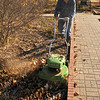 Phil Galbreath uses a mower to mulch leaves and debris at Dillingham Garden Wednesday. (Staff Photo by BILLY HEFTON)