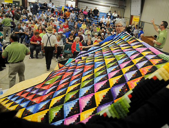 Oklahoma Mennonite Relief Sale volunteers hold the People's Choice quilt as Lippard Auctioneers accept bids from buyers Saturday at the Chisholm Trail Expo Center Pavilion. The pieced, hand quilted, log cabin pattern quilt, which sold for $3900, was made and donated by Vonita Unruh from the First Mennonite Church in Clinton.  Proceeds from the annual event support Mennonite disaster relief projects around the world. (Staff Photo by BONNIE VCULEK)