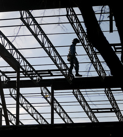 A welder's silhouette appears as he walks the second story steel framing at the new Enid High School University Center Thursday. (Staff Photo by BONNIE VCULEK)