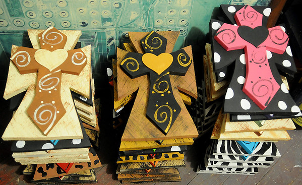 Unique crosses, created by Jamie Davis, owner of Lola's Boutique & Tanning, are ready for the Home for the Holiday Craft Show in Enid. Davis offers custom designs for her clients upon request. (Staff Photo by BONNIE VCULEK)